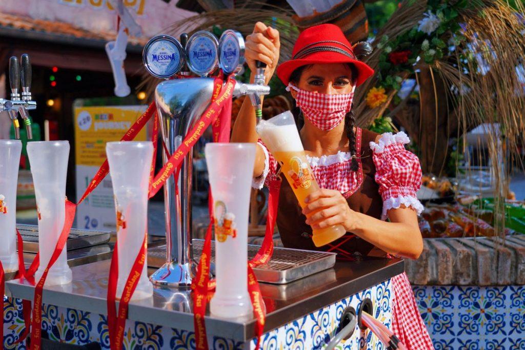 Ragazza in costume bavarese spilla birra durante l'evento Gardaland Oktoberfest