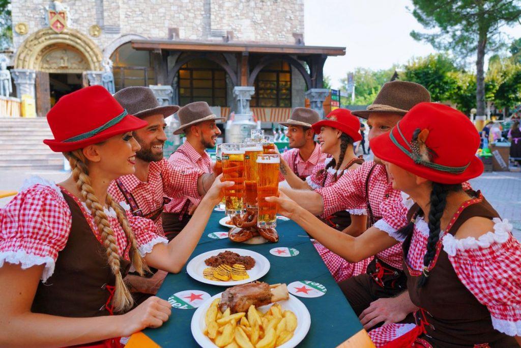 Gruppo di ragazze e ragazzi degustano cibi tipici bavaresi durante la festa della birra a Gardaland